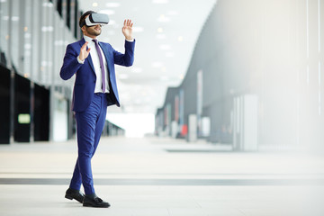 Businessman in elegant blue suit and vr headset taking part in virtual conference while moving inside modern building