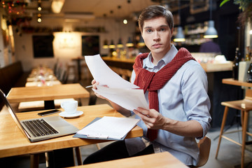 Portrait of businessman reading documents while sitting at coffee shop