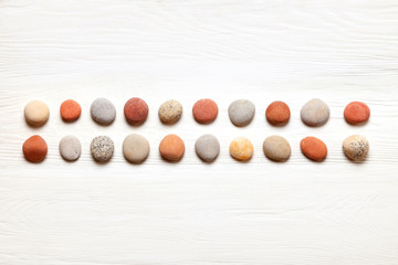 pattern of colored pebbles on white wooden background. Flat lay, top view