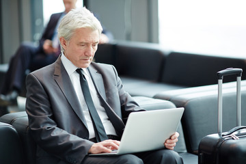 Senior businessman sitting in airport lounge with laptop in front and browsing in the net
