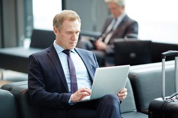 Elegant mature businessman watching webcast in laptop while waiting for airplane in lounge
