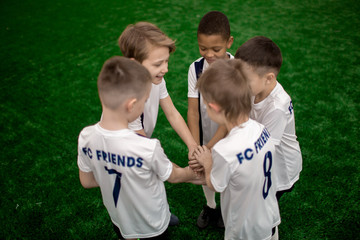 Football team of five little players standing in circle and making pile of hands