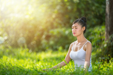 Woman sitting in yoga in lawn-- relax in nature.female happiness.