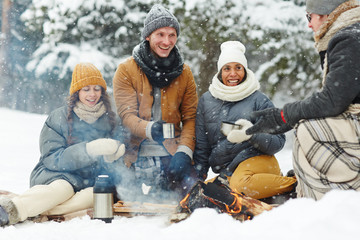 Joyful young people in winterwear sitting in snow arounf fire and having hot drinks