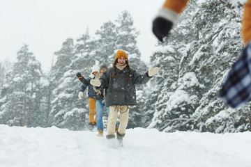Cheerful friends running in snowdrift while having fun in winter forest on weekend