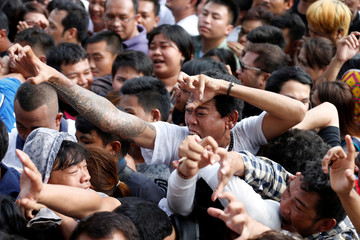Devotees are sprayed with holy water during a religious tattoo festival at Wat Bang Phra monastery, where devotees come to recharge the power of their sacred tattoos, in Nakhon Pathom province