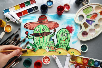 man draws a family cactus with funny faces in the desert. watercolor
