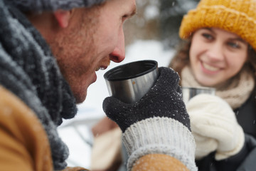 Young traveler drinking hot tea while enjoying trip in the forest with his girlfriend