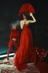 Beautiful model wearing red dress and crown is posing in a dark surreal studio