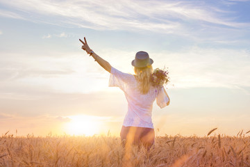 Beauty girl outdoors enjoying nature. Beautiful girl in blouse and hat, standing on the field of spring, autumn. Solar backlight. The concept of freedom. Copy space