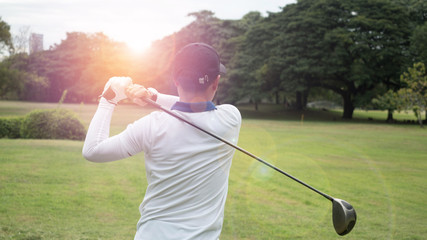 Golf player hitting beautiful shot with club on course with sun flare in background
