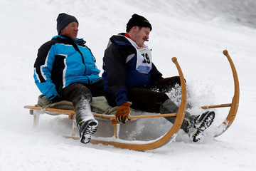 A crew member of a traditional wooden sledge competition smokes a cigar during the 21st 'Hornschlitten' race in Grindelwald