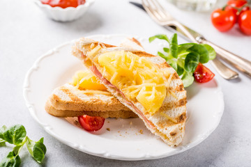 Hot fresh hawaii toast sandwich with ham, pineapple, tomato and cheese. Healthy summer food concept.