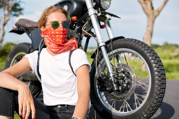 Portrait of stylish female biker wears bandana and sunglasses, sits near fast motorbike, looks pensively away, has rest in open air after long ride, enjoys freedom and high speed. Hobby concept