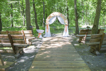 Simple but beautiful and romantic wedding arch decorated with flowers and pearls in rustic style inside forest trees on a daylight. Copy space