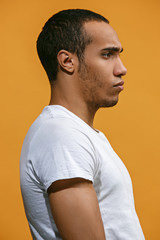 Serious Afro-American man is looking serious against orange background