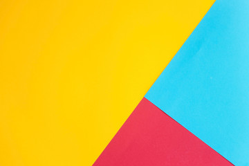 Yellow background with a red and blue part. Bright, geometric, minimalistic. Smooth paper texture. Flat lay. Top view