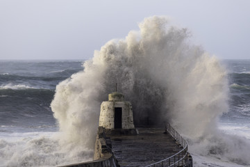 Wave breaks over Pepper Pot on Portreath harbor wall