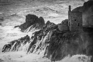 Wave drains off rocks at Botallack monochrome