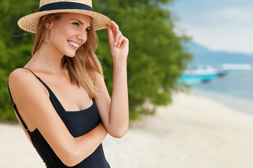 Outdoor shot of slim woman with positive expression, dressed in black bikini and straw hat, looks into distance as stands near ocean, admires soft waves and sunshine. Summer and resort concept