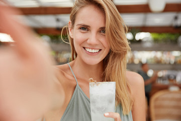 Pretty young blonde woman with pleasant smile, drinks fresh cold cocktail, makes selfie and sits against cafe interior. Cheerful glad female recreats during summer time, enjoys exotic beverage