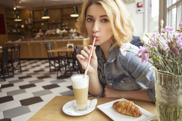 Blonde (with dark roots) caucasian woman in casual summer outfit at the cafe. Grey dress and jeans jacket. Woman got natural day makeup and curly hairstyle. She drinks coffee latte and eats croissant