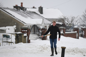 A man walks with a shovel to help dig out houses that are submerged in snow near Dublin