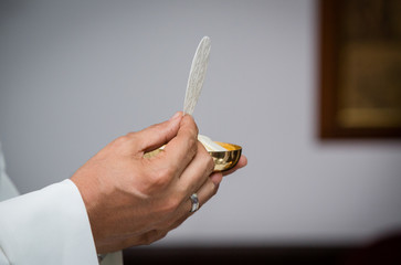 Closeup of priest with communion in the hand - Religious ceremony