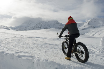 man use electric bicycle, e-bike, ebike, pedal on snow covered road, downhill mountain, specific bike with wide wheels to go on snow, called fatbike, winter, cold, alps, Simplon Pass, Switzerland