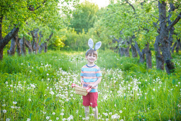 cheerful boy holding basket full of colorful easter eggs standing on the grass in the park after egg hunt