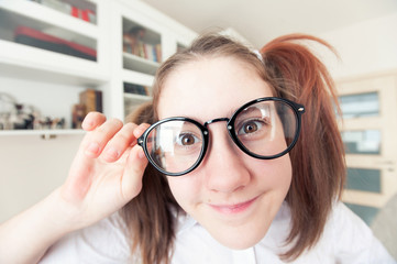 Portrait of funny pretty nerdy girl with ponytails in glasses