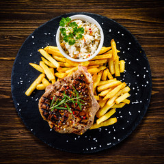 Grilled steak with french fries and vegetables served on black stone on wooden table