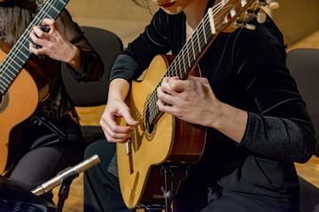 two young women playing guitar