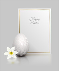 White color realistic egg with silver metallic floral pattern and Happy Easter card golden frame. White narcissus flower on light grey background with reflection. Vintage banner, card. Simple design.