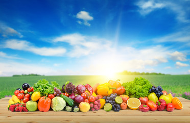 Vegetables and fruit on wooden table of boards against background of spring field