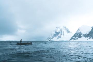 Man steering Rubber Dinghy through the Polar Landscape - Antarctica