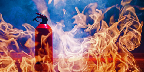 a fire extinguisher stands in a room, flames and strong smoke develop