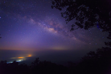 The Milky Way Galaxy and silhouette of trees in the mountains. Night scene landscape at Doi Dam view point Chiang mai, Thailand.