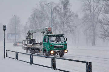 Truck with manipulator moves along a snowy road in a Blizzard