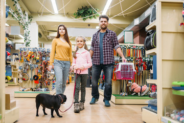 Family buying supplies for puppy in pet shop