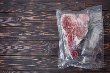 Vacuum sealed fresh beef meat on wooden background. Top view