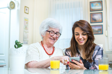 Cheerful teenage girl showing something on mobile phone to her grandmother at home.