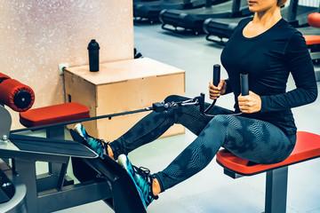 Athletic woman does lat exercises on gym machine