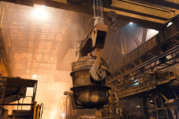 Melting of metal in a steel plant. High temperature in the melting furnace. Metallurgical industry. Factory for the manufacture of metal pipes. Bucket for feeding metal into molds.