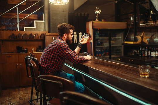 Man sitting at the bar counter and drink alcohol