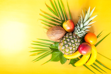 Flat lay of various tropical fruits on palm leaves. Pineapple, mango, banans, orange, apple and strawberries. Yellow background. Copy space. Horizontal.