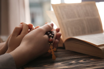 Religious Christian girl with her mother holding rosary beads at table, closeup