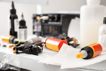 Tattoo machine and bottles with ink on table, closeup