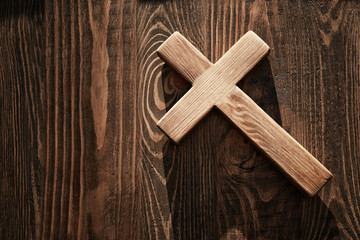 Cross on wooden background, top view