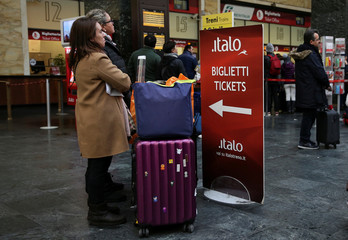 Two women wait next to a banner displaying where to buy Italo train tickets at the Santa Lucia train station in Florence